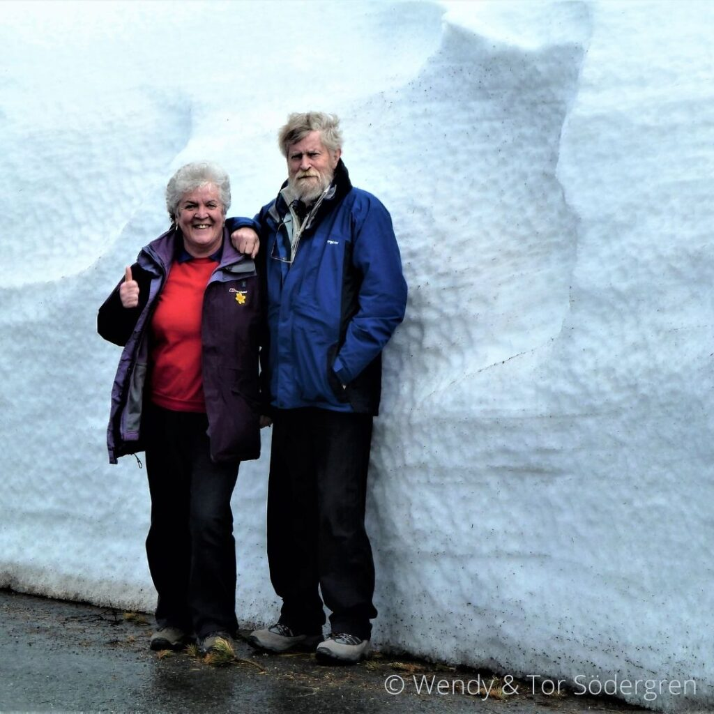 Wendy and Tor in front of a tall block of snow.